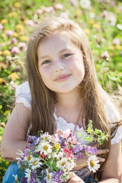 Retrato De Uma Menina De Crianca De Sete Anos De Idade Feliz Pequeno Bonito Com Tremoco Flores De Flor Em Um Campo Na Natureza Ao Ar Livre Foto Premium