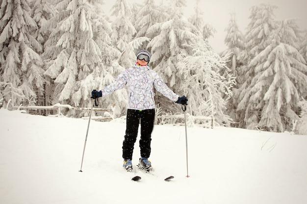 Retrato de uma menina de pé em esquis e posando contra florestas e montanhas nevadas. natureza do inverno nas montanhas dos cárpatos. mulher é esquiadora. queda de neve forte. Foto Premium
