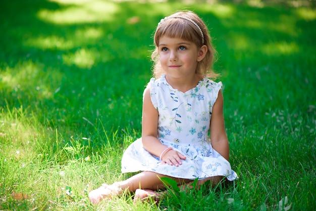 Retrato de uma menina de sorriso que senta-se na grama verde. Foto Premium