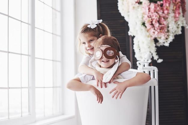 Retrato de uma menina e um menino de chapéu piloto jogando no banheiro em pilotos ou marinheiros. viagens, infância e realização de sonhos Foto Premium