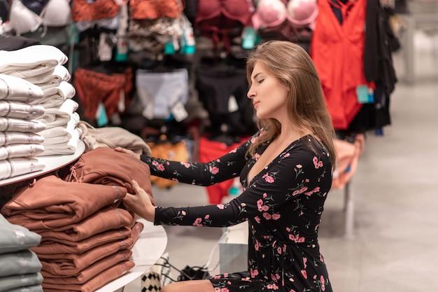 Retrato de uma menina elegante em perfil posando meio sentado perto do rack com as coisas e seleciona roupas da pilha proposta de coisas. venda. compras. dia de descontos. Foto Premium
