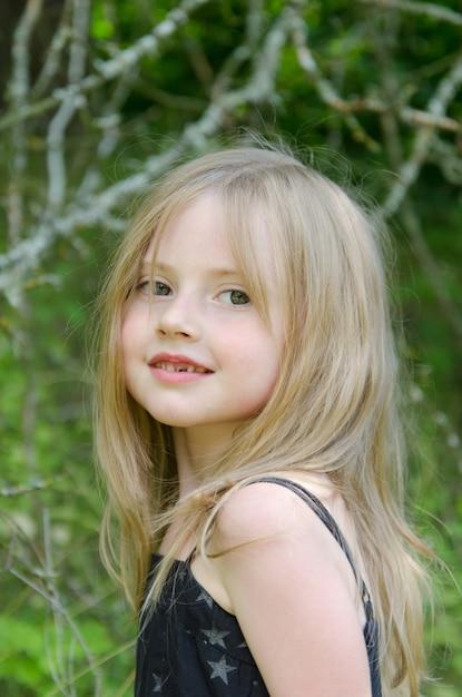 Retrato de uma menina em um campo de verão com decorações de flores do campo Foto Premium