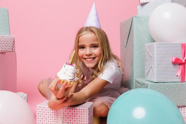 Retrato de uma menina em um chapéu de aniversário comemorando Foto gratuita
