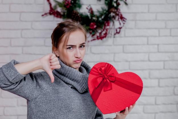 Retrato de uma menina em um suéter cinza com uma caixa de presente vermelha em forma de coração, sentado no apartamento, conceito de dia dos namorados, cópia espaço Foto Premium