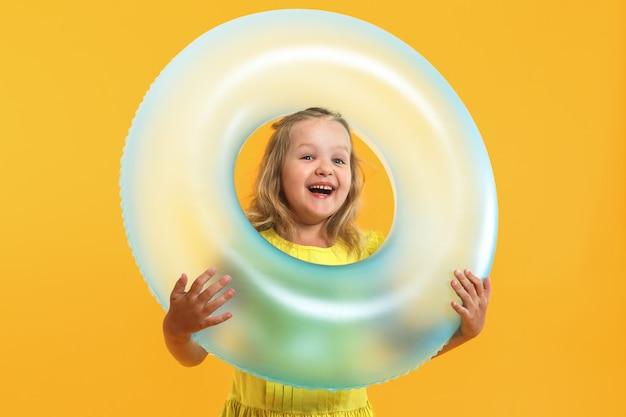 Retrato de uma menina em um vestido com um anel de natação. Foto Premium