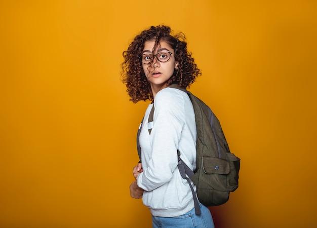 Retrato de uma menina estudante indiano indiano surpreso em copos com uma mochila. Foto Premium