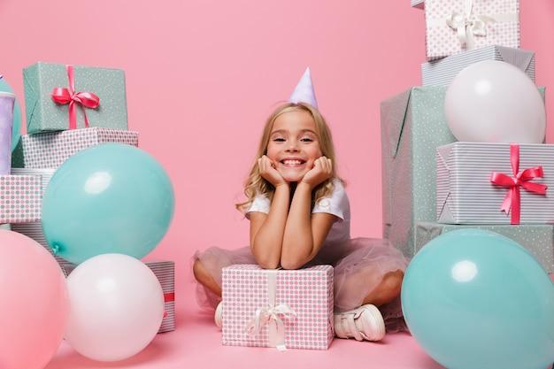 Retrato de uma menina feliz em um chapéu de aniversário Foto gratuita