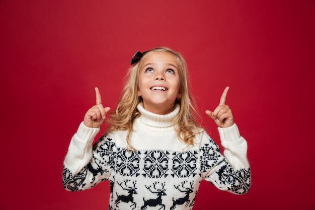 Retrato de uma menina feliz na camisola de natal Foto gratuita