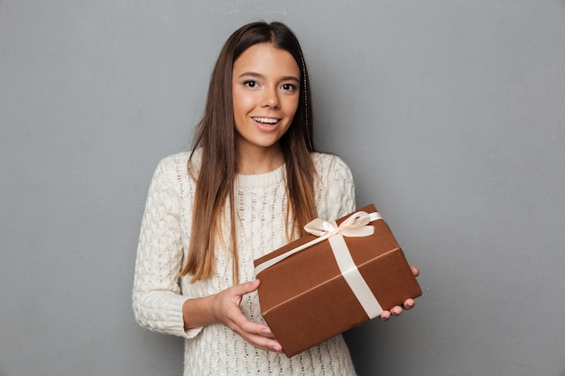 Retrato de uma menina feliz na camisola segurando a caixa de presente Foto gratuita