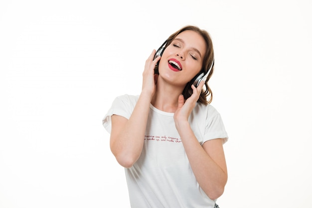 Retrato de uma menina feliz ouvindo música com fones de ouvido Foto gratuita