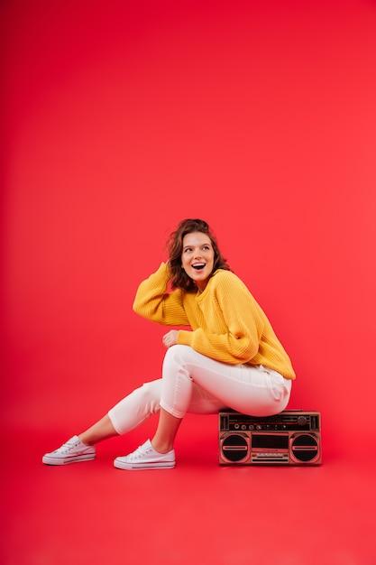 Retrato de uma menina feliz, sentado em um boombox Foto gratuita