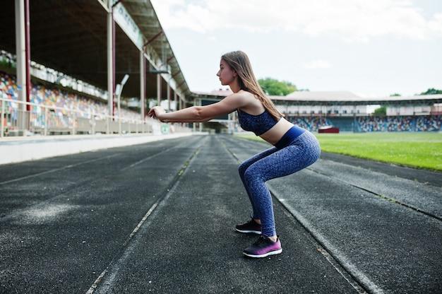 Retrato de uma menina linda fazendo agachamentos no estádio. Foto Premium