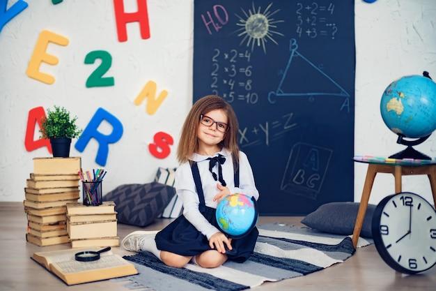 Retrato de uma menina linda jovem estudante segurando o globo sentado no chão no tapete. Foto Premium