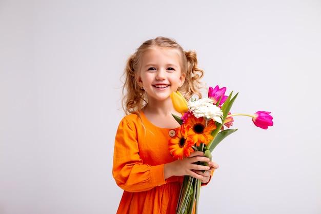 Retrato de uma menina loira com um buquê de flores da primavera em uma parede de luz Foto Premium