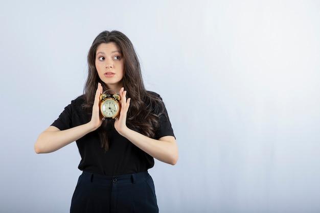 Retrato de uma menina morena com roupa preta segurando um relógio e posando em cinza Foto gratuita