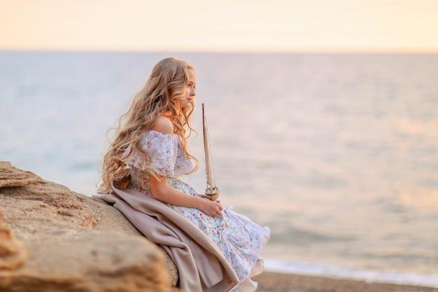 Retrato de uma menina perto do mar, sentado nas rochas com um navio de brinquedo nas mãos. Foto Premium