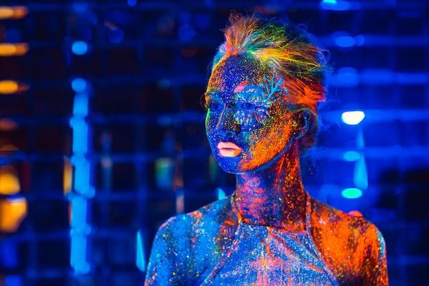 Retrato de uma menina pintada em pó fluorescente. Foto Premium