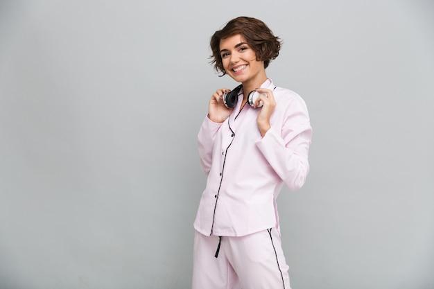 Retrato de uma menina sorridente alegre de pijama com fones de ouvido Foto gratuita