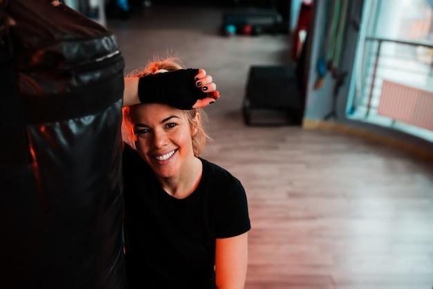 Retrato de uma menina sorridente, apoiando-se em um saco de pancadas. olhando para a câmera. Foto Premium
