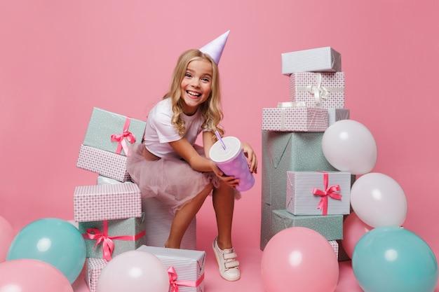 Retrato de uma menina sorridente em um chapéu de aniversário Foto gratuita