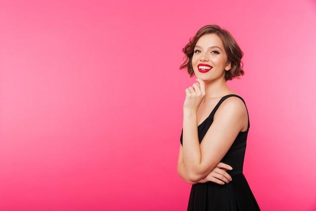 Retrato de uma menina sorridente, vestida de vestido preto Foto gratuita