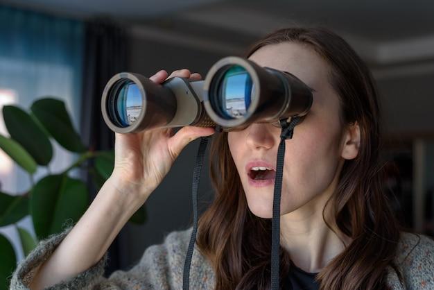 Retrato de uma morena surpresa com binóculos, olhando pela janela, espionando vizinhos Foto Premium