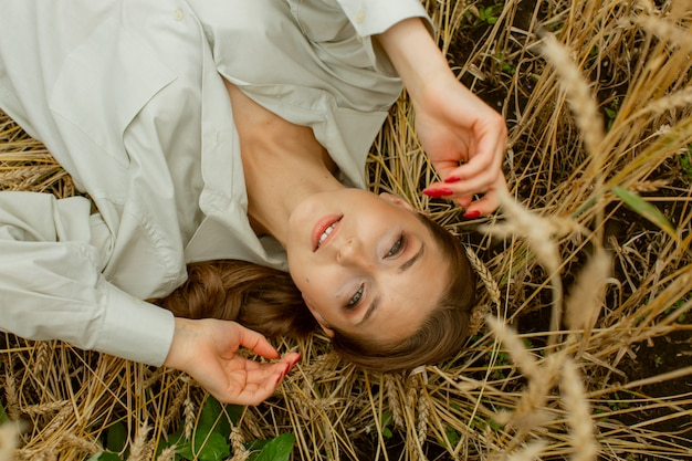 Retrato de uma mulher adorável agradável que segura o cabelo com a mão, que é soprada pelo vento. ela fica no telhado e sorri. Foto Premium