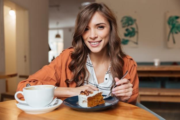 Retrato de uma mulher alegre, comer pedaço de bolo Foto gratuita