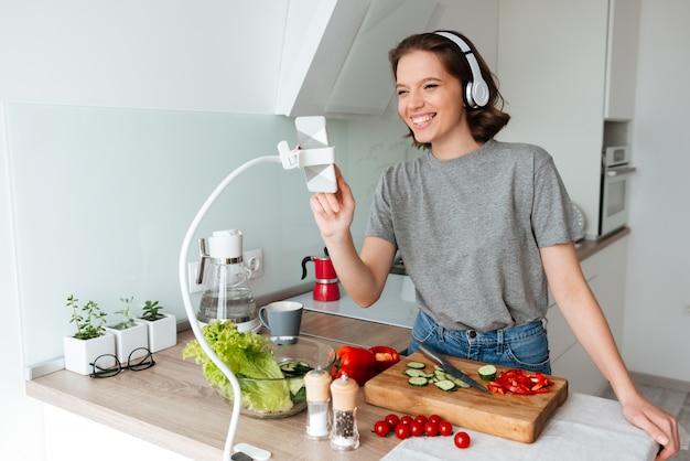 Retrato de uma mulher alegre e feliz com fones de ouvido Foto gratuita