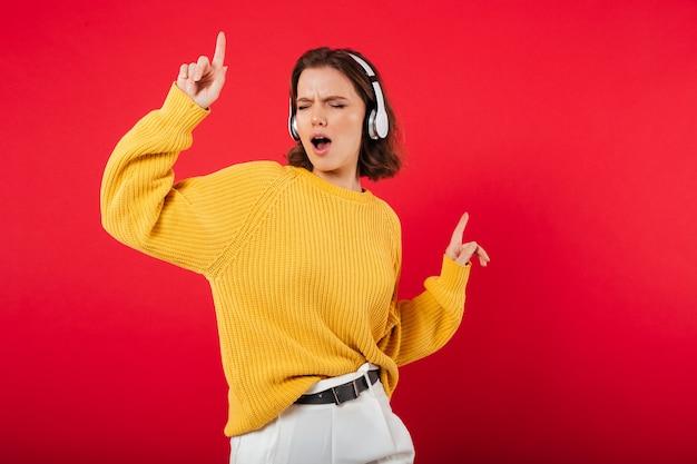 Retrato de uma mulher alegre em fones de ouvido Foto gratuita