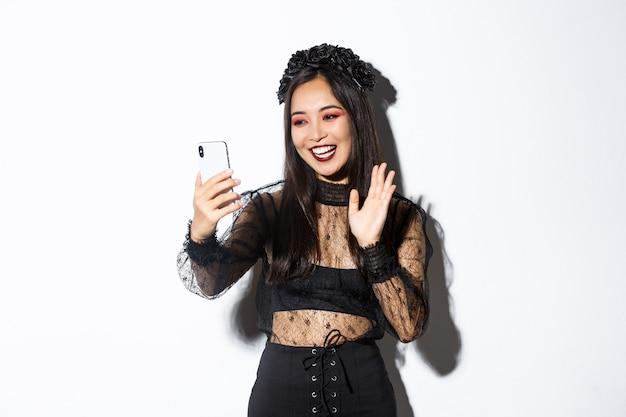 Retrato de uma mulher asiática bonita e elegante em renda gótica vestido dizendo olá, acenando com a mão para a câmera do smartphone durante a chamada de vídeo, em pé sobre um fundo branco. Foto gratuita