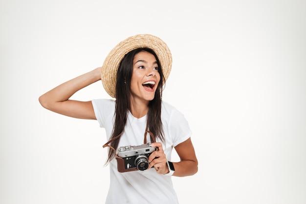 Retrato de uma mulher atraente no chapéu segurando uma câmera Foto gratuita