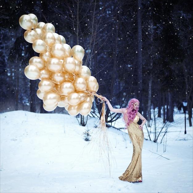 Retrato de uma mulher bonita com cabelo rosa em dourado vestido longo elegante com penteado Foto Premium