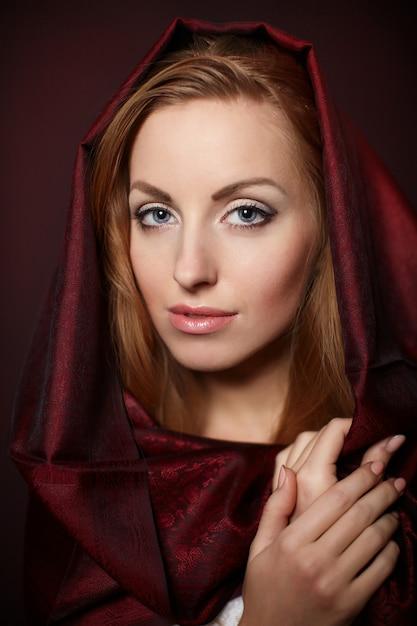Retrato de uma mulher bonita com maquiagem de noite. modelo posando no estúdio com têxteis vermelhos na cabeça Foto gratuita
