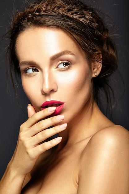 Retrato de uma mulher bonita com maquiagem diária fresca tocando sua boca Foto gratuita
