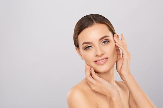 Retrato de uma mulher bonita com maquiagem natural tocando seu rosto. Foto Premium