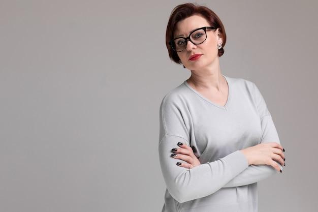 Retrato de uma mulher bonita com óculos isolado na luz Foto Premium