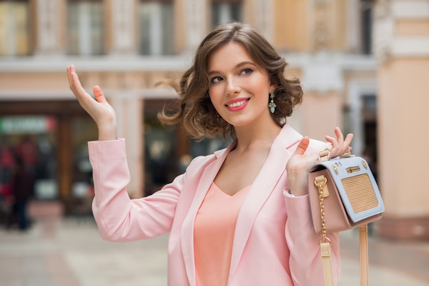 Retrato de uma mulher bonita e elegante caminhando no centro da cidade com uma jaqueta rosa segurando uma bolsa, tendência da moda verão, sorrindo, feliz, maquiagem natural, balançando o cabelo caído, senhora elegante, clima romântico Foto gratuita