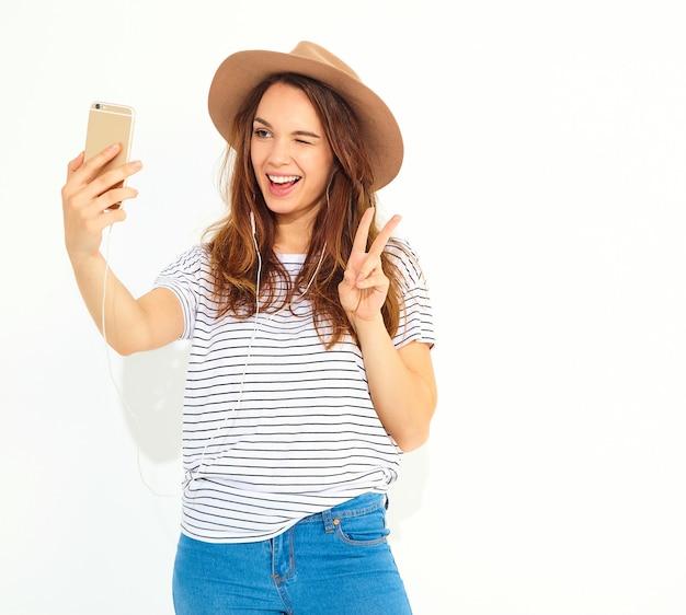 Retrato de uma mulher bonita em roupas de hipster de verão tomando uma selfie isolada na parede branca. piscando e mostrando sinal de paz Foto gratuita