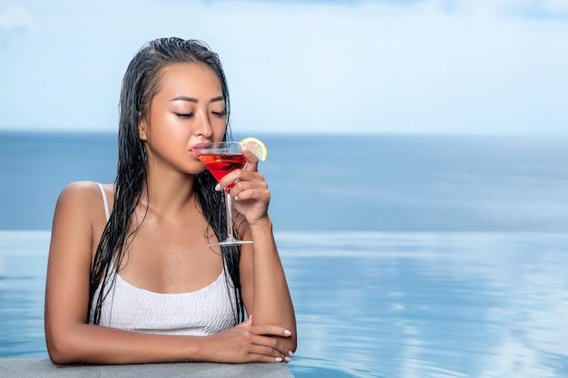 Retrato de uma mulher bonita em um top branco que bebe de cocktail cosmopolita. vista para o mar em fundo desfocado. piscina infinita nos fundos desfocados Foto Premium