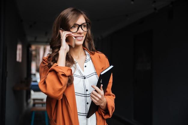 Retrato de uma mulher casual, falando no celular Foto gratuita