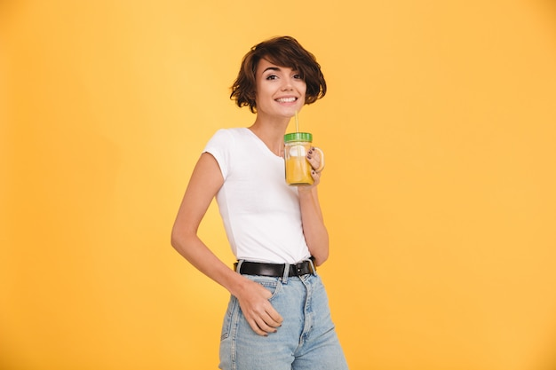 Retrato de uma mulher casual sorridente bebendo laranja Foto gratuita