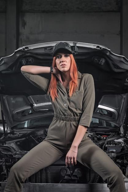 Retrato de uma mulher de beleza em jeans curtos e top em um fundo de oficina. Foto Premium