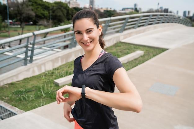 Retrato de uma mulher de fitness, verificando as horas no relógio inteligente. esporte e conceito de estilo de vida saudável. Foto Premium