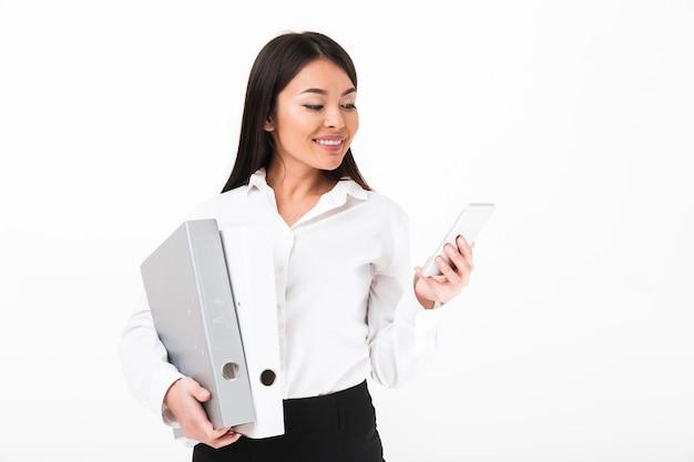 Retrato de uma mulher de negócios asiática sorridente segurando pastas Foto gratuita