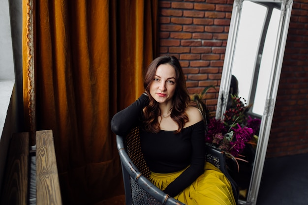 Retrato de uma mulher elegante deslumbrante sentado em uma cadeira Foto gratuita