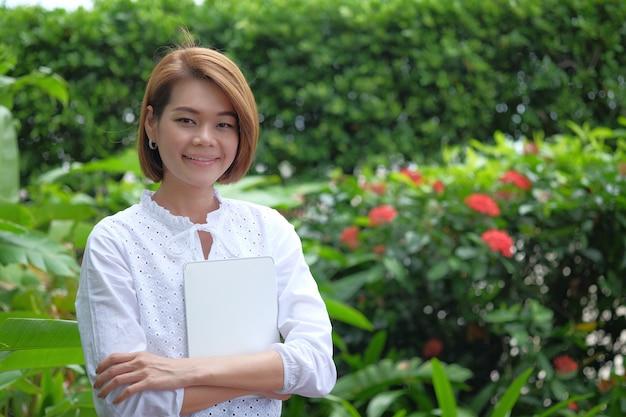 Retrato de uma mulher em pé segurando um tablet pc. mulher sorridente no exterior verde com espaço de cópia Foto Premium
