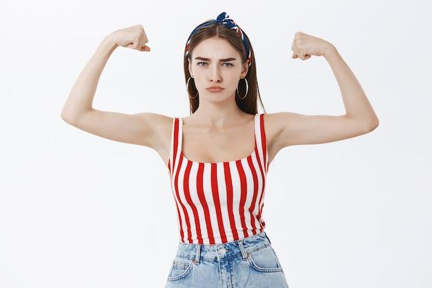Retrato de uma mulher europeia elegante, forte e confiante, bonita, com um top listrado e uma faixa na cabeça franzindo os lábios e franzindo a testa fazendo uma careta mostrando os músculos e os bíceps Foto gratuita