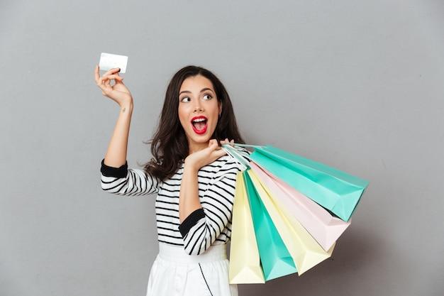 Retrato de uma mulher excitada, mostrando o cartão de crédito Foto gratuita