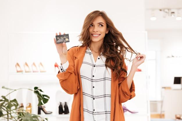 Retrato de uma mulher excitada segurando o cartão de crédito Foto gratuita